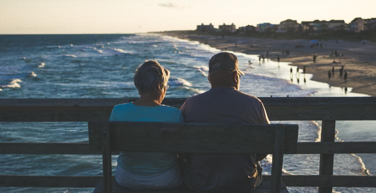 two people sitting on the beach looking at a beach