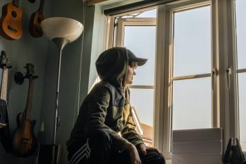 young person looking through the window