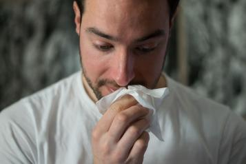 man with flu holding tissue to his face