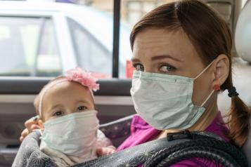 woman and baby with face masks