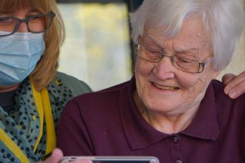 carer looking at phone together with elderly woman
