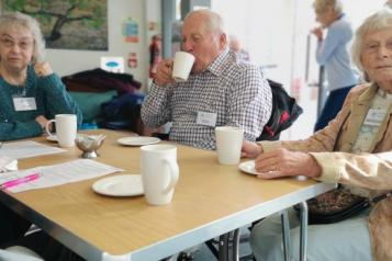 3 elderly people sitting at a table drinking tea