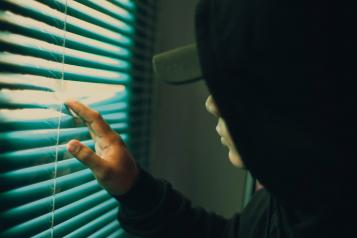 young man next to window with fingers in blinds looking outside