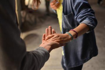 one person giving their hand to another person