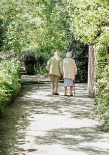 two elderly people walking in a park